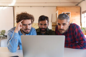 Group of male entrepreneurs in casual staring at laptop monitor. Business colleagues in casual meeting in contemporary office space