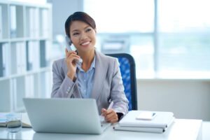 Portrait of smiling young female business executive talking on the phone in her office