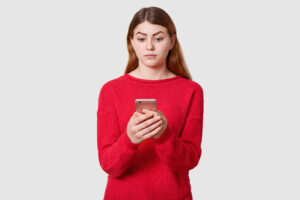 Portrait of confused cute woman with dark straight hair, wears red sweater, holds mobile phone in hand, looking at its display, isolated over white studio background